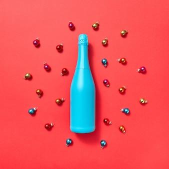 A composição da decoração da garrafa pintada de azul sobre um fundo vermelho cobriu as bolas coloridas de vidro do ano novo com espaço de cópia. cartão de natal