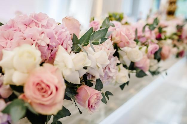 A composição de flores roxas, rosa e vegetação em pé na mesa servida na área da festa de casamento. mesa de recém-casados servida com pratos e talheres. fechar-se.
