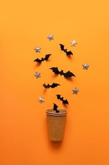 A composição do feriado de halloween de bastões pretos voa fora do copo de papel na superfície alaranjada.