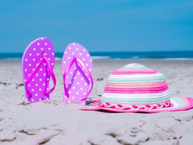 A composição do verão com cccessories da praia encalha chinelos e chapéu colorido na areia tropical contra a parede azul do mar e do céu. conceito de férias de verão de férias na praia, passeio no mar, verão ensolarado quente.