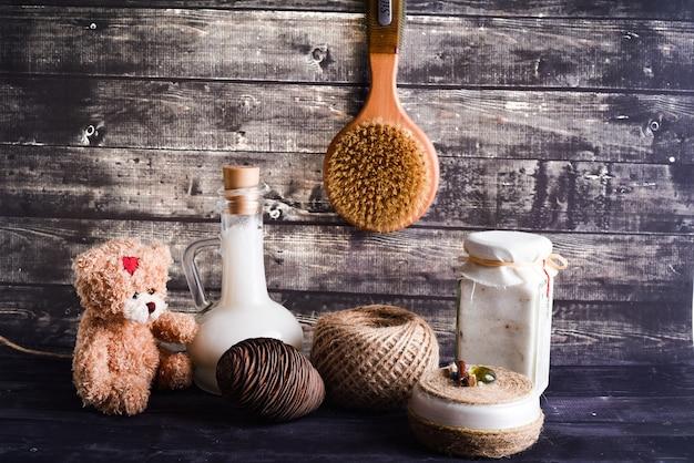 A composição leiga com produtos para o corpo. um pote de creme natural, uma garrafa de óleo de coco, uma moeda de pinho e um ursinho de pelúcia