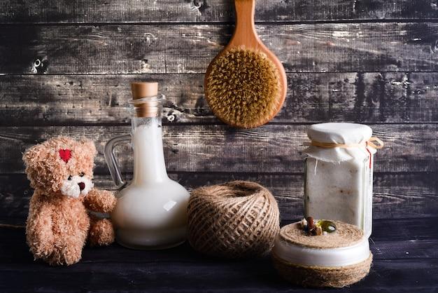 A composição leiga com produtos para o corpo. um pote de creme natural, ursinho de pelúcia marrom, uma garrafa de óleo de coco e escova para lavar