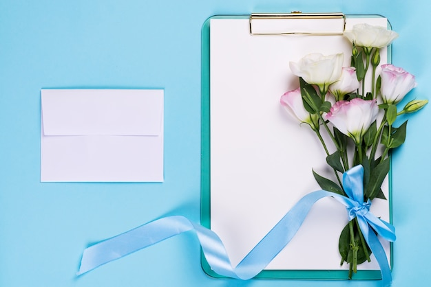 A composição mínima com um eustoma floresce em um envelope com prancheta em um fundo azul, vista superior. dia dos namorados, aniversário, mãe ou cartão de felicitações de casamento