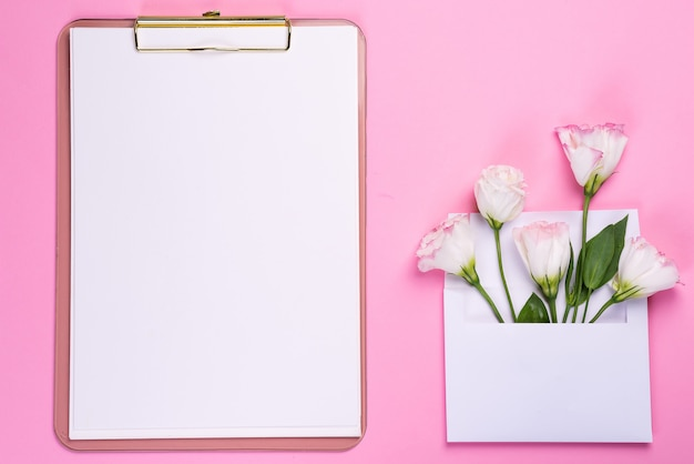 A composição mínima com um eustoma floresce em um envelope com prancheta em um fundo cor-de-rosa, vista superior. dia dos namorados, aniversário, mãe ou cartão de felicitações de casamento