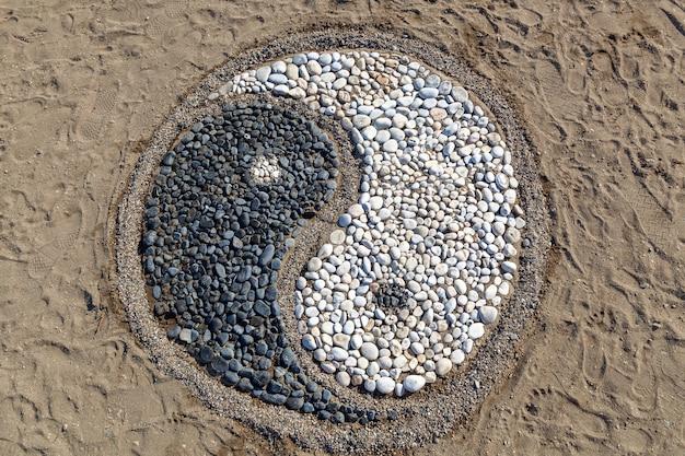 A concepção de yin e yang é assentada com pedras na areia, yin e yang de pedras