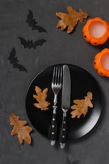 A configuração da mesa de halloween é decorada com velas em forma de abóbora, morcegos e folhas de carvalho na mesa escura. formato vertical