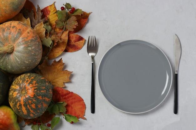 A configuração da mesa no dia de ação de graças decorou uma abóbora e folhas coloridas na superfície cinza