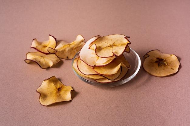 A configuração lisa de maçãs secadas lasca-se em um frasco de vidro sobre o fundo cor-de-rosa.