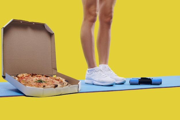 A construção muscular se encaixa nas pernas da mulher em pé sobre um tapete de ioga perto de uma caixa de pizza fresca saborosa e halteres. conceito de perder peso e engordar. conceito de fitness e dieta.