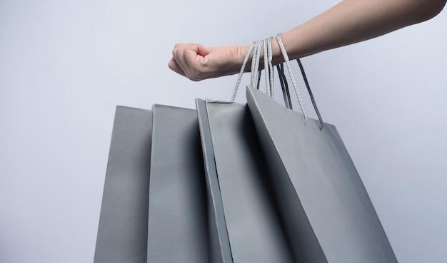 A cor cinza da sacola de compras segura pelo braço da mulher asiática de negócios e o fundo branco representa as compras
