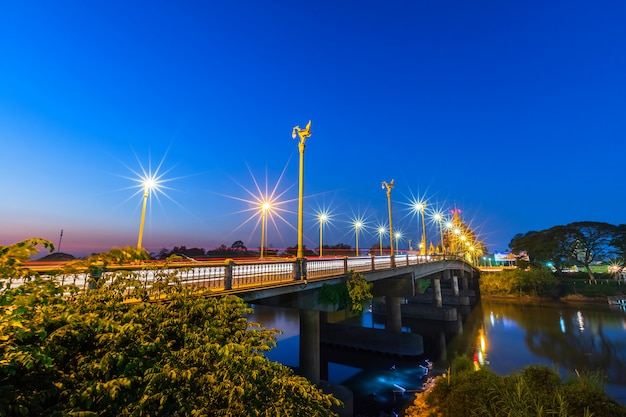 A cor do semáforo da noite na estrada na ponte