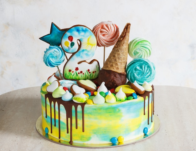 A cor moderna do arco-íris do bolo das crianças no branco com merengue de madeira
