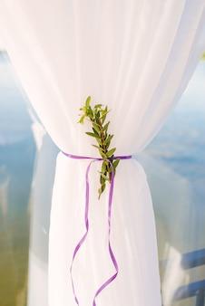 A cortina branca está reunida sob uma fita de cetim roxa com um raminho de close-up verde. detalhe interior