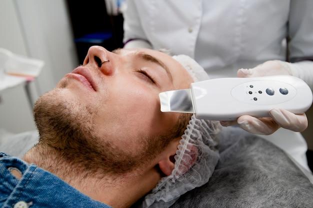 A cosmetologista está limpando o rosto do jovem de acne e cicatrizes por ultrassom.