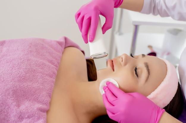 A cosmetologista faz o procedimento de descamação facial ultrassônica da pele do rosto de uma bela e jovem mulher em um salão de beleza.