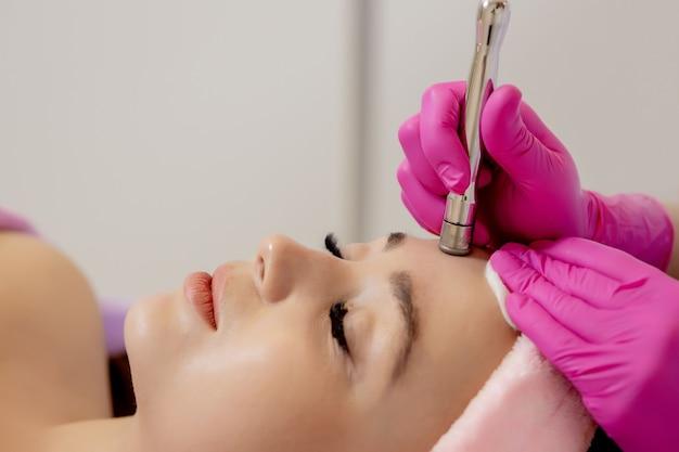 A cosmetologista faz o procedimento de microdermoabrasão da pele do rosto de uma bela e jovem mulher em um salão de beleza.