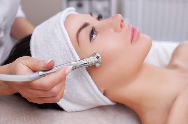 A cosmetologista faz o procedimento de microdermoabrasão da pele facial de uma bela