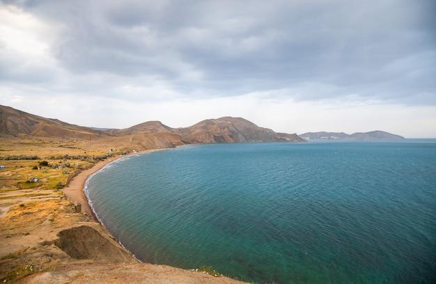 A costa do mar negro na crimeia, em koktebel no camaleão do cabo ao pôr do sol