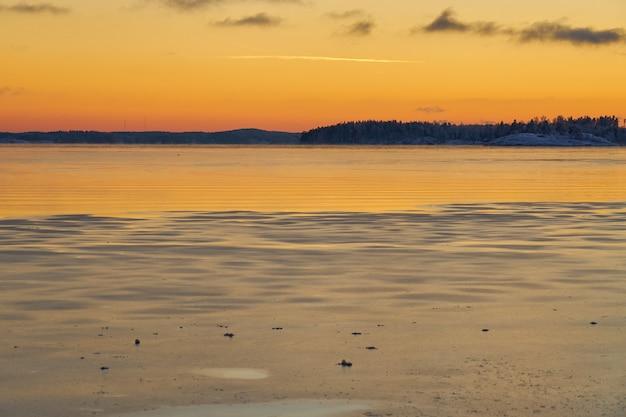 A costa do mar no gelo e na neve ao pôr do sol