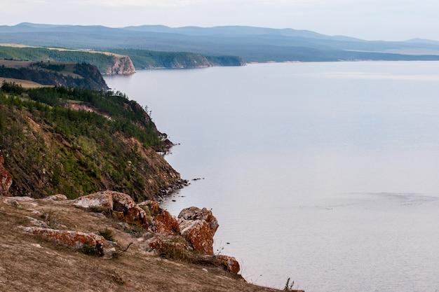 A costa rochosa do lago baikal com pedras salientes e musgo vermelho sobre elas. a costa está coberta de floresta. afaste a névoa.