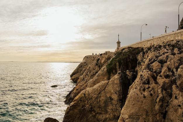 A costa rochosa e as águas azul-turquesa aqua ao longo da costa de nice, frança
