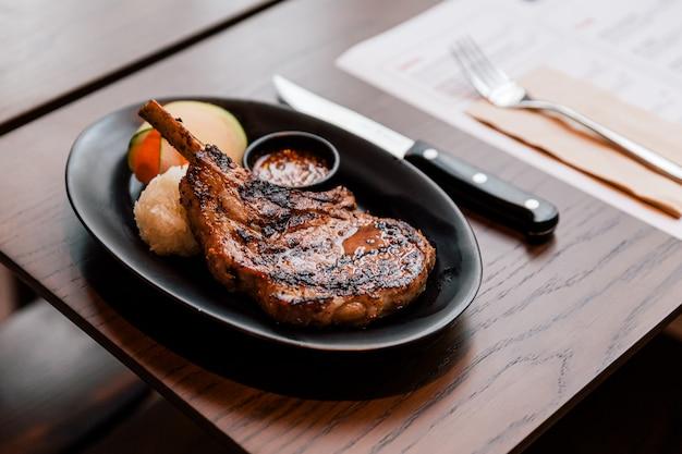 A costeleta de carne de porco tailandesa do bbq do estilo serviu com arroz pegajoso, cortou a cenoura e o molho picante tailandês.
