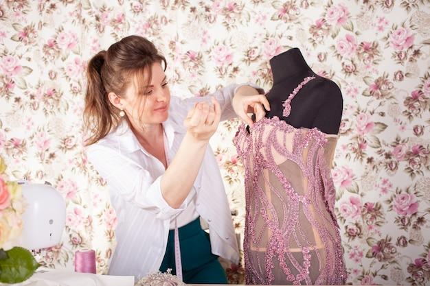 A costureira costura renda e miçangas no vestido rosa