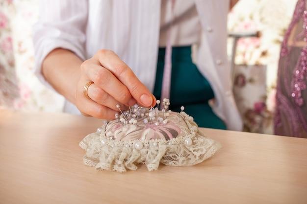 A costureira do ateliê tira um alfinete de uma linda almofada de renda feita de agulha