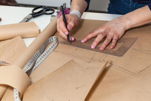 A costureira está cortando o desenho de um vestido com uma tesoura. desenvolvimento de estilo e design e criação de vestuário, serviço de costura e conserto de roupas, conceito de costureira no trabalho