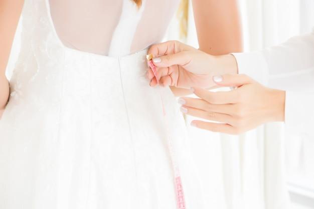 A costureira está usando uma fita métrica para uma mulher em um vestido de noiva cortar seu vestido de noiva.