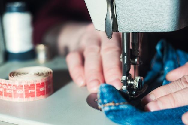 A costureira idosa está trabalhando na máquina de costura