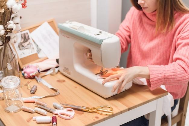 A costureira trabalha em uma máquina de costura. a mulher costura e segura um pano rosa