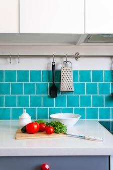 A cozinha apresenta armários frontais planos cinza escuro combinados com bancadas de quartzo branco e um azulejo azul brilhante.