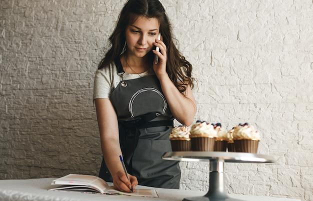 A cozinheira está falando ao telefone, anotando um pedido de um cliente.