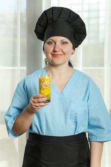 A cozinheira está segurando um copo com um coquetel de frutas na mão.