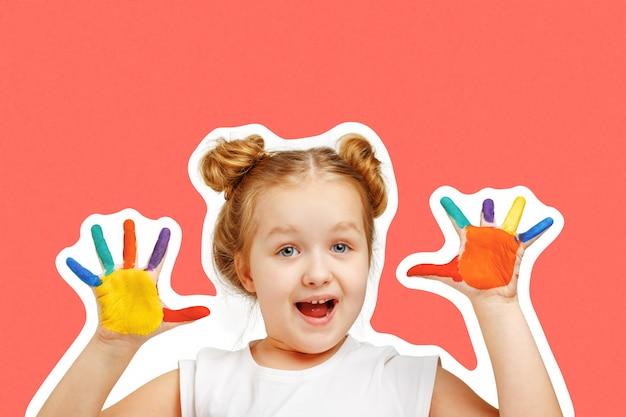 A criança alegre da menina mostra as mãos pintadas com pintura.