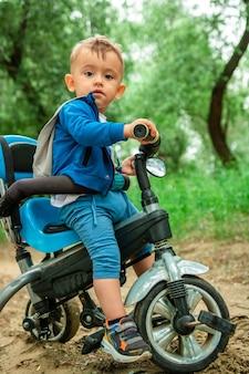 A criança anda de bicicleta na floresta