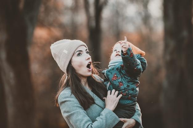 A criança aponta para o topo e a mãe fica surpresa.