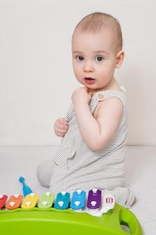 A criança aprende a tocar xilofone. bebê estudando entusiasticamente um instrumento musical