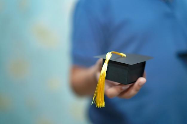 A criança asiática das crianças prende o chapéu da abertura da graduação à disposicão.