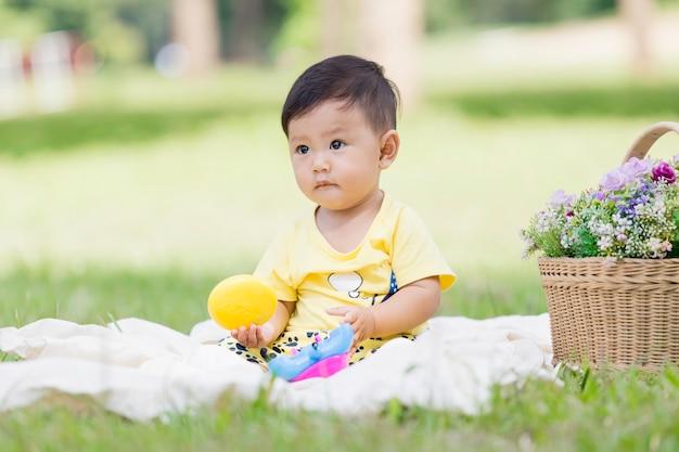 A criança asiática de sorriso do cabelo e dos olhos do menino asiático senta-se no algodão branco na grama verde apenas e que joga o brinquedo.