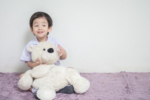 A criança asiática do close up com a cara excited com boneca do urso senta-se no tapete