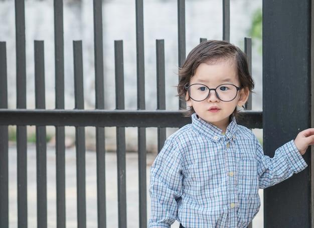 A criança asiática do close up com óculos está na frente do fundo textured da cerca de aço