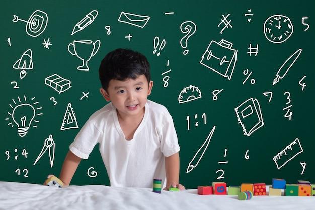A criança asiática que aprende jogando com sua imaginação sobre artigos de papelaria fornece atividades do objeto da escola para aprender