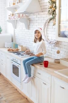 A criança assa e prova biscoitos de natal