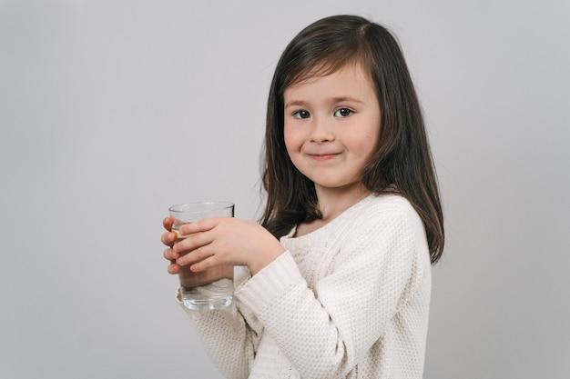 A criança bebe água de um copo. uma garota de cabelo escuro segura um copo d'água. a morena leva um estilo de vida saudável