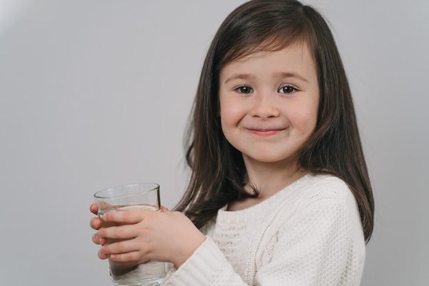 A criança bebe água de um copo. uma garota de cabelo escuro segura um copo d'água.