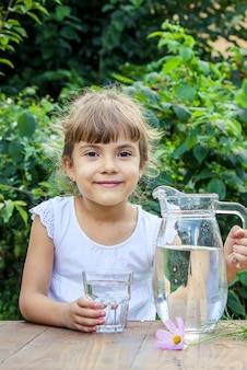 A criança bebe água limpa no verão. foco seletivo.