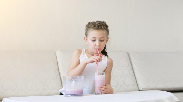 A criança bebe um coquetel com um canudo.