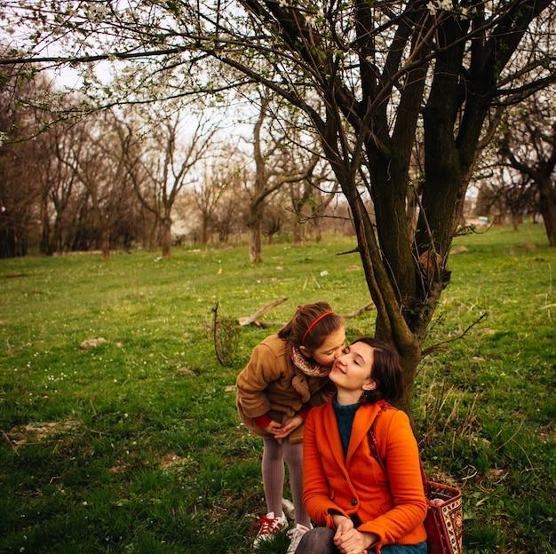 A criança bonita beijando sua mãe